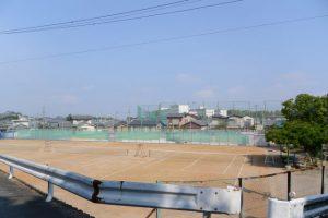 宇治山田高校のテニスコートおよび遠くに見える校舎