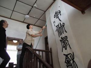 高潤生さんがパフォーマンスで書き上げた作品「気淑風和」の展示作業(伊勢和紙ギャラリー)