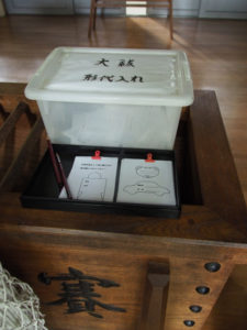 賽銭箱の上に置かれた大祓の形代用紙、日保見山八幡宮(伊勢市大湊)